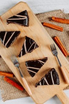 Fette di torta al cioccolato in una tavola di legno e pezzo di sacco con bastoncini di cannella e forchette vista dall'alto su uno sfondo bianco