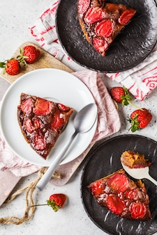 Fette di torta alle fragole su piattini bianchi e neri