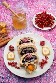 Fette di torta rotolo vista dall'alto in lontananza con diversi frutti all'interno del piatto bianco con miele sulla frutta dolce del biscotto della torta colorata scrivania