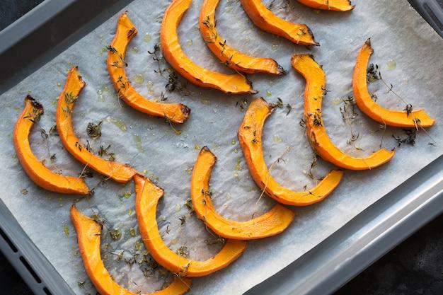 Fette di zucca arrosto a caldo con timo, olio d'oliva e sale su carta da forno. gustoso cibo vegano.