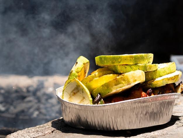 Fette di zucchine arrostite sul piatto di alluminio il giorno soleggiato