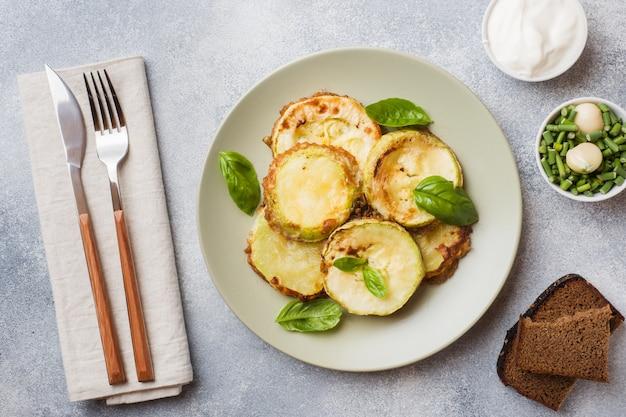 Fette di zucchine fritte in pastella con aglio e basilico su un piatto.