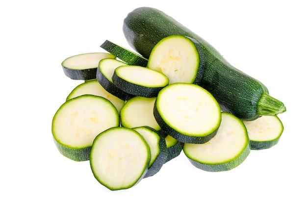 Fette di zucchine tritate su sfondo bianco come elemento del pacchetto
