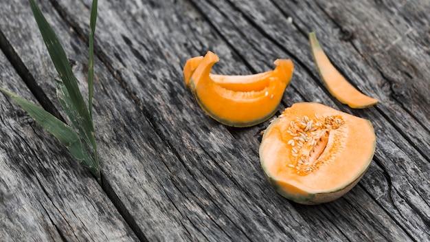 Fette e dimezzato di melone su un vecchio fondale in legno