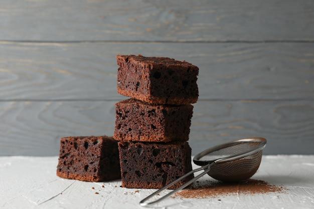 Fette e filtro del dolce di cioccolato sulla tavola bianca, fine su