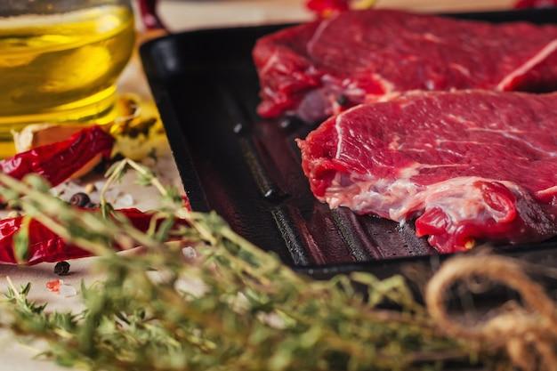 Fette fresche della carne cruda sulla vista superiore della padella. bistecche di manzo pronte per la cottura con olio d'oliva