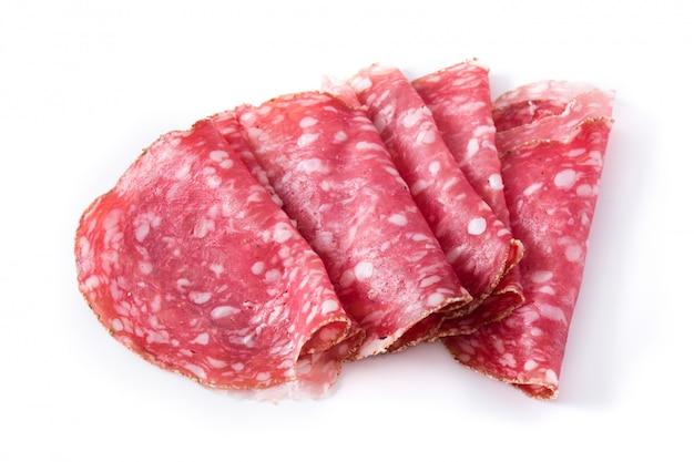 Fette fresche della salsiccia del salame su superficie bianca