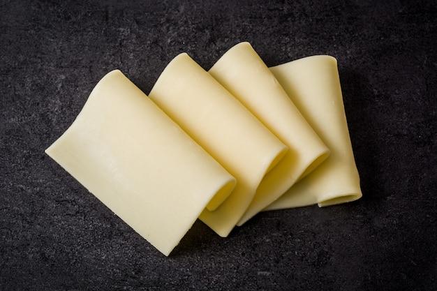 Fette gialle del formaggio sull'ardesia nera