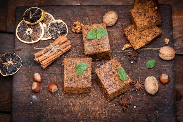 Fette quadrate al forno di una torta whith noci su un bordo di legno bianco, pan di spagna