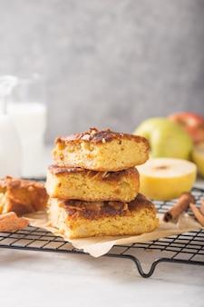 Fette quadrate della torta di mele dei brownie del blondie (biondo) casalinghe con bicchiere di latte