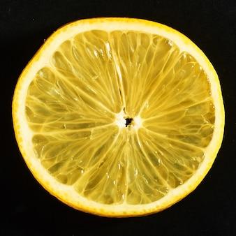 Fette succose fresche di limone su un nero.