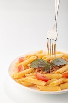 Fettuccine alla bolognese con salsa al pomodoro e basilico in piatto bianco su bianco