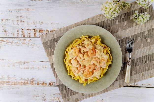Fettuccine con salsa di alfredo e gamberi sul piatto.