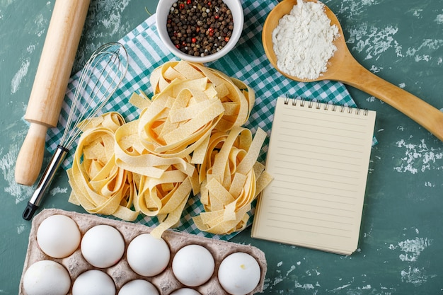 Fettuccine con uova, mattarello, frusta, grani di pepe, amido e quaderno