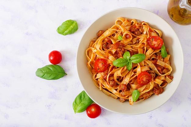 Fettuccine di pasta alla bolognese con salsa di pomodoro in una ciotola bianca.