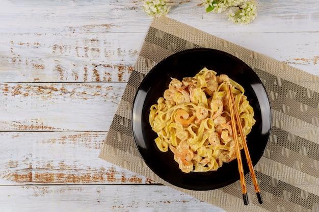 Fettuccine di pasta con salsa di alfredo e gamberi in banda nera.
