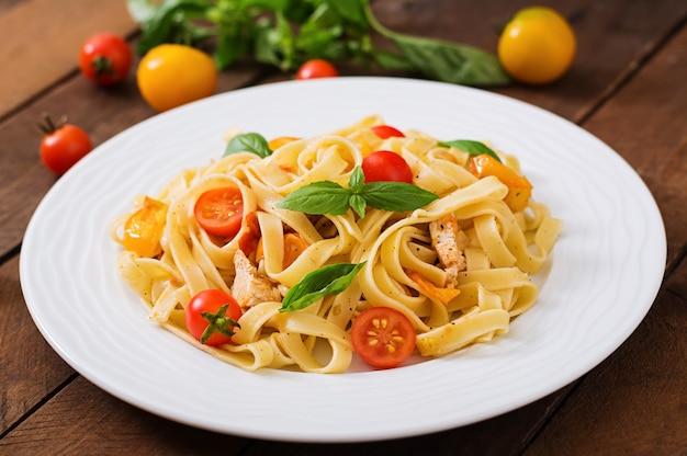Fettuccine in salsa di pomodoro con pollo, pomodori decorati con tavolo al basilico