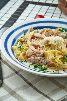 Fettuccine italiane in salsa di formaggio con parmigiano, pollo e prosciutto, erbe in ciotola di ceramica bianca sulla superficie bianca.