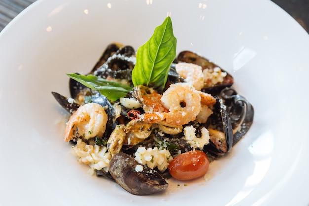 Fettuccine nere con gamberi, calamari e vongole. pasta al nero di seppia e frutti di mare.