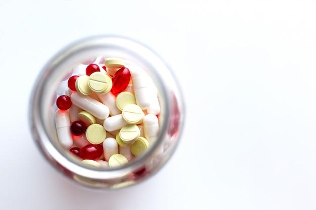 Fiala trasparente con capsule bianche, compresse gialle, capsule rosse e pillole, vista dall'alto