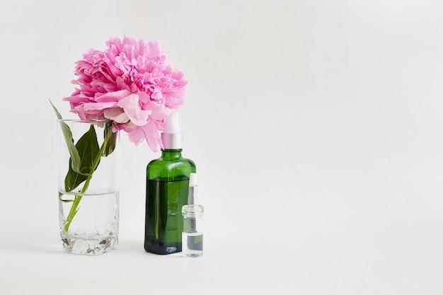 Fiala verde in vetro e fiori con olio per il corpo.