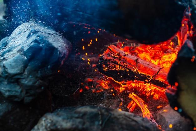 Fiamma arancione del fuoco. falò dall'interno. fumo e braci ardenti nell'aria.