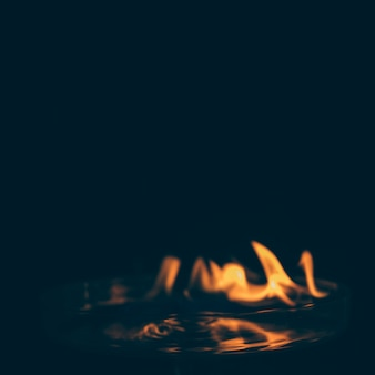 Fiamma ardente con acqua su fondo nero