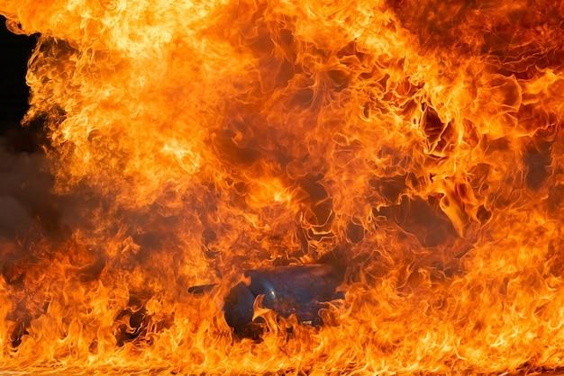 Fiamma bruciante del fuoco con olio combustibile, benzina che brucia nel contenitore,