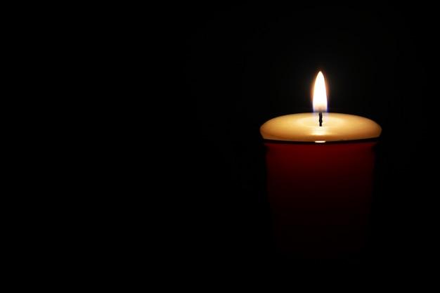 Fiamma di candela, candela accesa all'interno di un piccolo vetro rosso su fondo nero