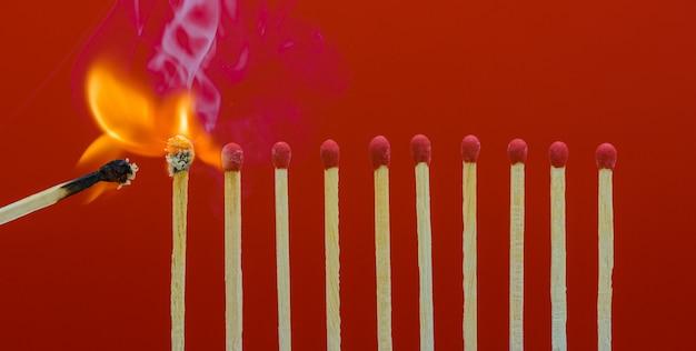 Fiammiferi che bruciano dando fuoco ai suoi vicini