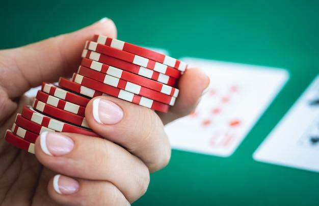 Fiches del casinò sul tavolo da poker tenuto dalla mano del giocatore