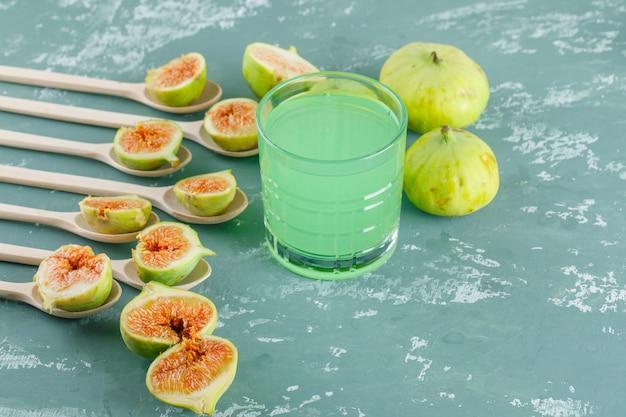 Fichi con bicchiere di bevanda in cucchiai di legno sulla parete di gesso, vista dall'alto.