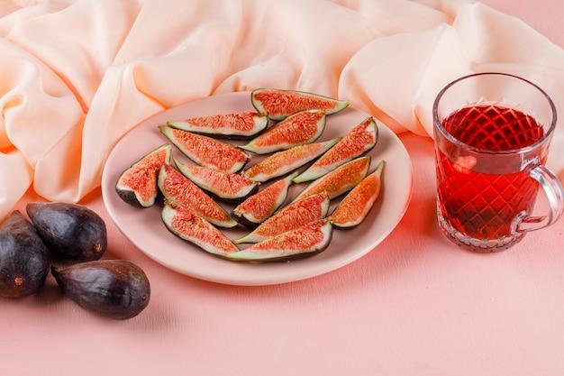 Fichi con la tazza di tè in un piatto sul rosa e sul tessuto, vista dell'angolo alto.
