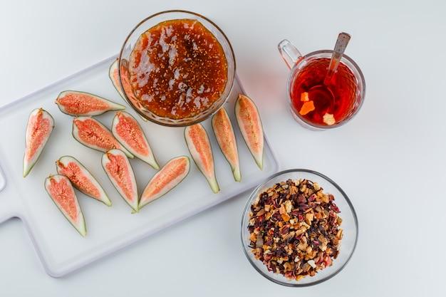 Fichi con marmellata di fichi, tè, cucchiaino, vista dall'alto di erbe secche su bianco e tagliere