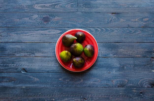 Fichi freschi con pesche, albicocche, mirtilli, fragole, su un tavolo di legno