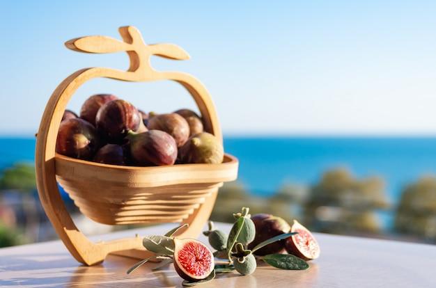 Fichi freschi. il fico fruttifica in un vaso di legno contro lo sfondo del mare