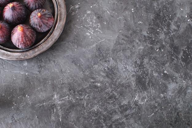 Fichi freschi sulla banda nera in ceramica sfondo nero di cemento