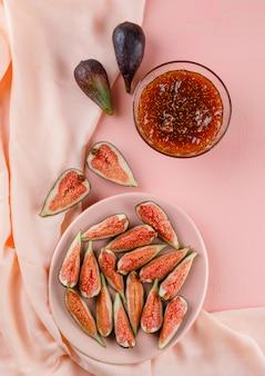 Fichi in un piatto con marmellata di fichi vista dall'alto su rosa e tessuto