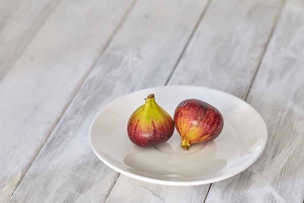 Fichi su un piatto sulla tavola di legno bianca
