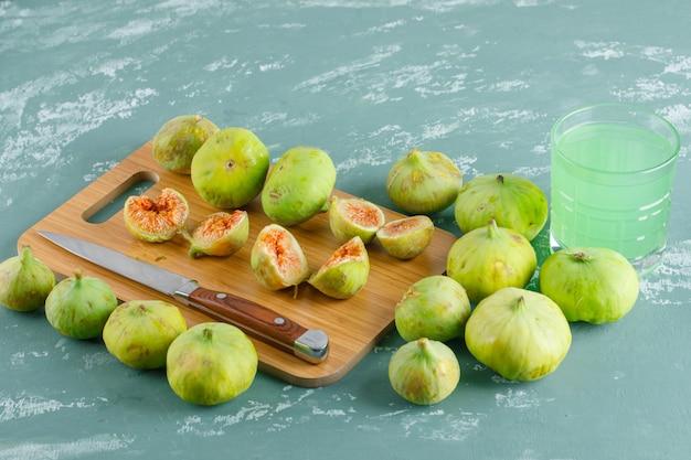 Fichi verdi con bevanda, coltello vista dall'alto su intonaco e tagliere