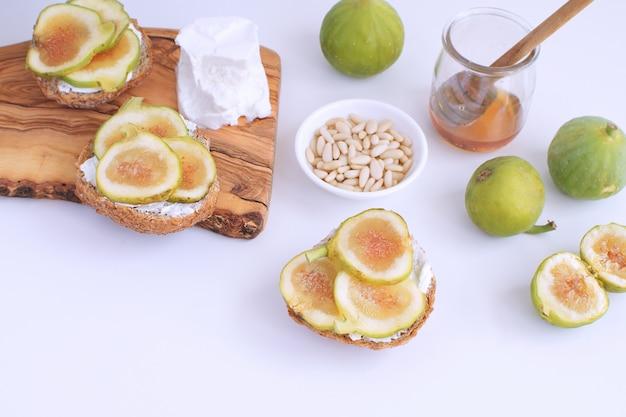 Fichi verdi freschi tagliere in legno pane integrale miele formaggio di capra pinoli