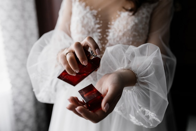 Fidanzata in abito bianco alla moda con belle maniche e profumo nelle mani