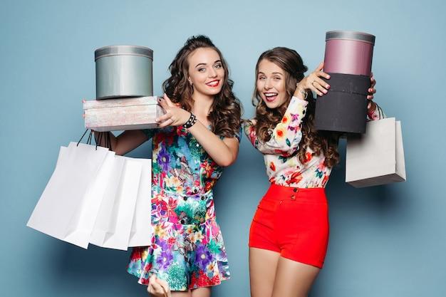 Fidanzate sorridenti in abiti colorati con molte borse dopo lo shopping.