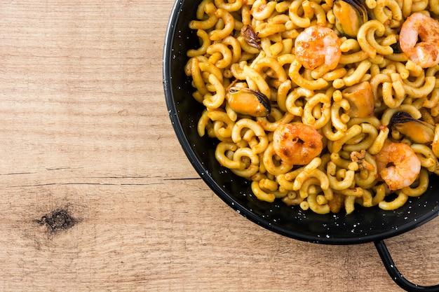 Fideua spagnola tradizionale. paella di pasta sulla tavola di legno. copia spazio