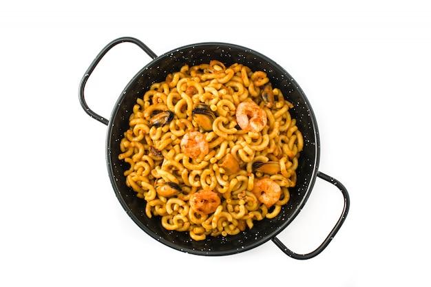 Fideua spagnolo tradizionale, paella della tagliatella isolata su bianco vista superiore