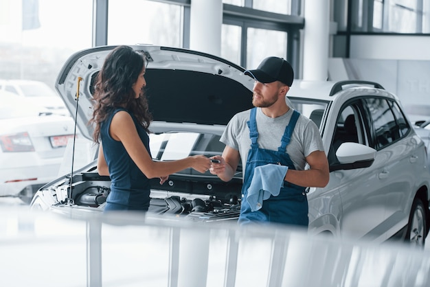 Fiducia e occupazione. donna nel salone dell'auto con dipendente in uniforme blu che riprende la sua auto riparata