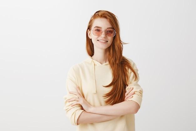 Fiduciosa donna alla moda rossa in occhiali da sole sorridente determinata