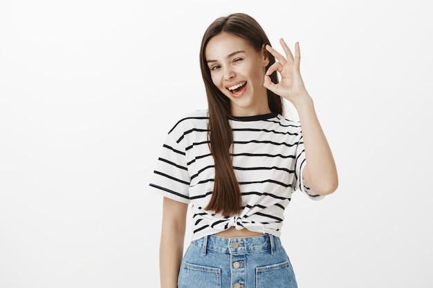 Fiduciosa giovane ragazza attraente che sorride e garantisce qualità, consiglia il prodotto, complimenta la scelta perfetta