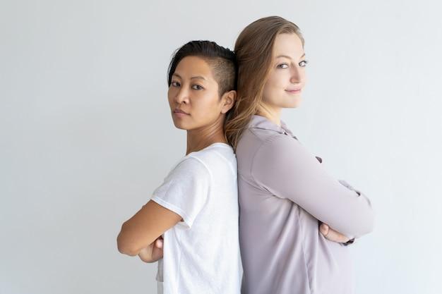 Fiduciose ragazze in piedi schiena contro schiena con le braccia incrociate