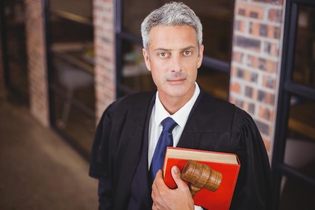 Fiducioso avvocato maschio con martelletto e libro rosso